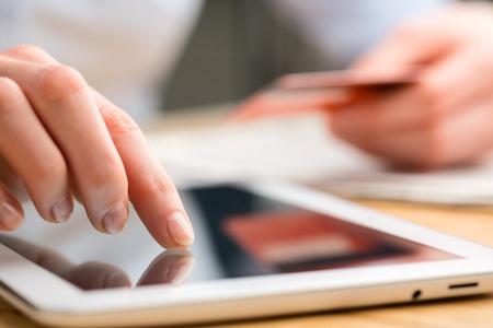タッチ スクリーンのタブレット コンピューターを介してクレジット カードで支払いの実業家のクローズ アップ画像。