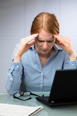 cansancio: Una joven mujer de negocios estresado mira hacia abajo y masajes a su cabeza en su lugar de trabajo.