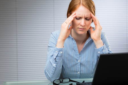 pains: A businesswoman with migraine pains rubs the side of her head while at work.