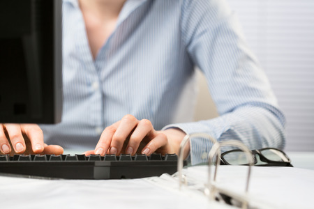 Closeup photograph of the hands of a young businesswoman typing on a keyboard over an office desk. Stock Photo