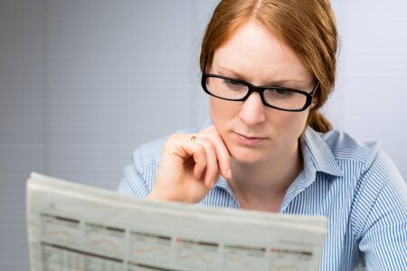 daily newspaper: A young business assistant carefully reads a daily newspaper at work. Stock Photo
