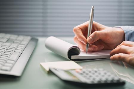 女性の手は、忙しいオフィスのデスクトップに紙のノートにメモをとります。低角度のクローズ アップ画像。