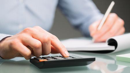 女性会計士は電卓を使用して、オフィスの机の上の紙のノートにメモをとります。
