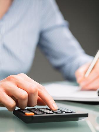여성 장관 또는 회계사가 계산기를 사용하고 종이 노트북에 메모를합니다. 근접 촬영 이미지입니다. 스톡 콘텐츠