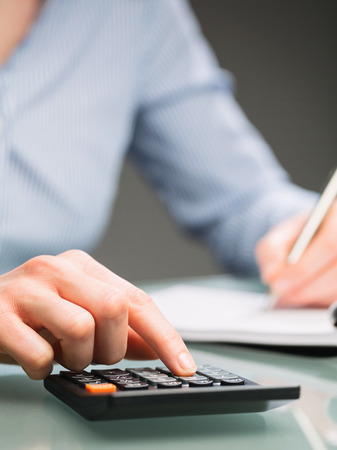 A female secretary or an accountant uses a calculator and takes notes on a paper notebook. Closeup image. Stock Photo