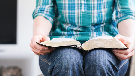 A young woman at home holds an open Bible in her lap. Closeup image with shallow DOF, focus on the tip of the book.