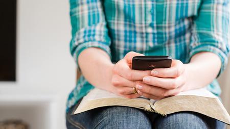 Een toevallige jonge vrouw maakt gebruik van een smartphone op een open Bijbel in huis. Stockfoto - 40809249