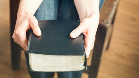 black bible: Female hands hold a black Bible. Closeup image.