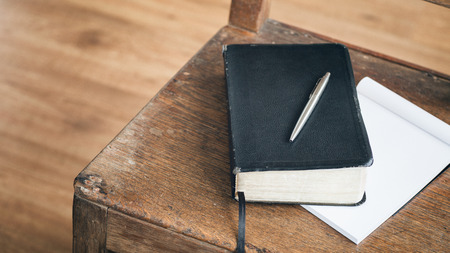 A black Bible with a pen rests over an open paper notebook on an old wooden chair. Stock Photo