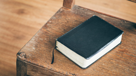 black bible: A black Bible on an old wooden chair.
