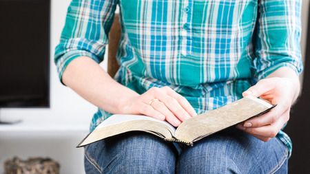 study: A casual young woman reads the Bible at home. Closeup image with shallow DOF, focus on the book.