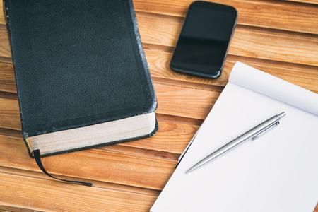 biblia: Materiales de estudio de la Biblia - una Biblia, cuaderno y un teléfono inteligente a través de una superficie de madera. Foto de archivo