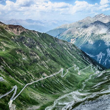 Alpine hills and the famous Stelvio pass road in Northern Italy, photographed by summer.