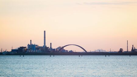 A large chemical factory with tall chimneys in the Venetian Lagoon, photographed by sunset. Stock Photo