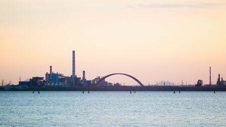 industria quimica: Una gran fábrica de productos químicos con altas chimeneas en la laguna de Venecia, fotografiado por la puesta del sol.