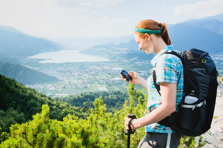handheld device: An active female tourist navigates on a scenic Alpine trail with a handheld GPS device.