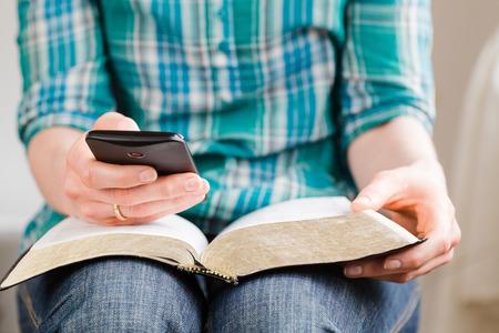 Een jonge vrouw bestudeert de Bijbel thuis met behulp van een smartphone. Ondiepe DOF, focus op de telefoon. Stockfoto