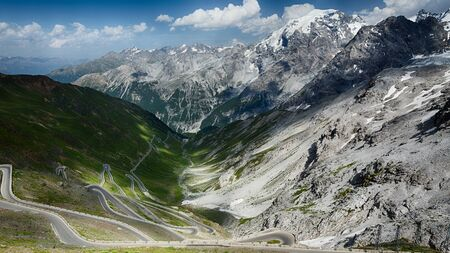 Dramatic scenery at the Stelvio pass road in Italy - clouds cast shadows over the valley.