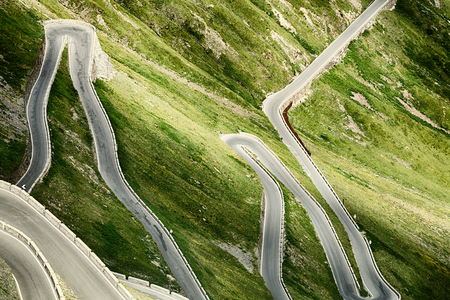 turns: Hairpin turns of the Stelvio pass road, surrounded by green hills by summer. Stock Photo