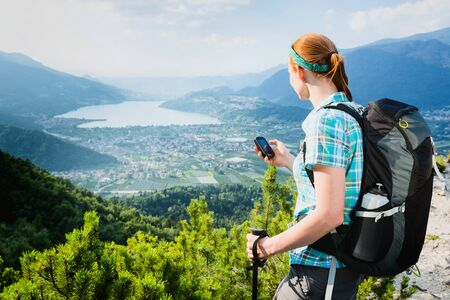 A woman holds an outdoor GPS navigation and looks at a scenic Alpine view over the lake Lago di Caldonazzo in Italy.