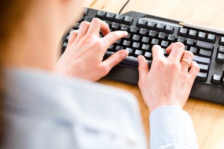 クローズ アップ、トップ角度木製デスクトップ上黒のコンピューター キーボードで入力してビジネスの女性観。