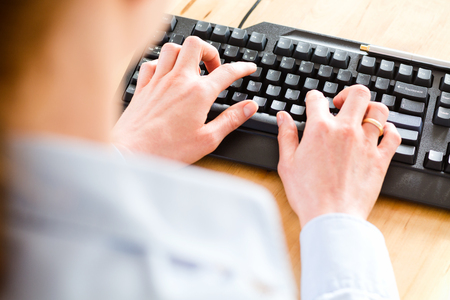 Closeup, top angle view of a business woman typing on a black computer keyboard over a wooden desktop.