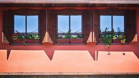 garret: Open wooden garret windows of an orange historic building in Koprivshtitsa, Bulgaria.