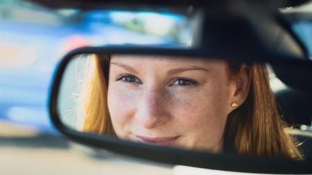 rear view mirror: Una mujer joven sonriente se sienta en un coche - reflejo en el espejo retrovisor.