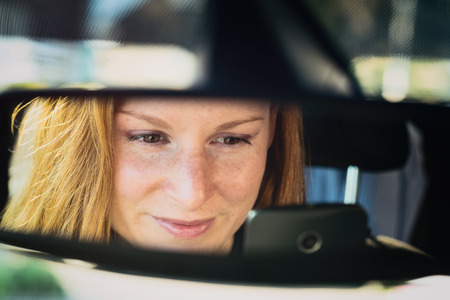 reckless: A reckless young female driver uses a mobile phone behind the steering wheel of a car. Closeup, reflection in the rear view mirror. Stock Photo