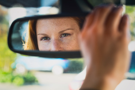 A young female car driver adjusts the rear view mirror with her hand.