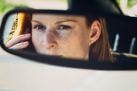 Serious woman talks on a mobile phone behind the steering wheel of a car. Reflection in the rear view mirror.