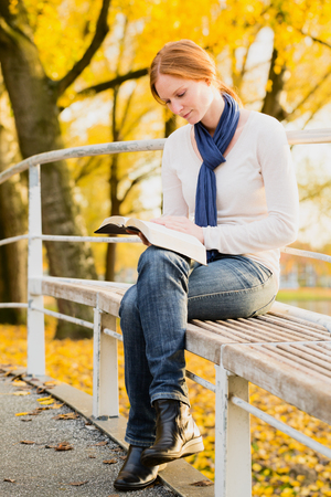 devotional: A young woman reading the Bible in a city park.