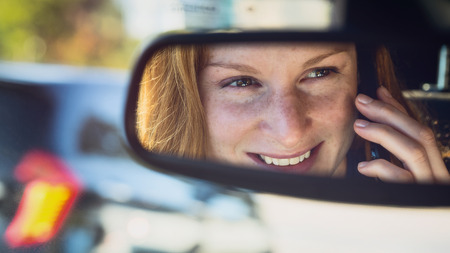 rear view mirror: Smiling young woman talks on a mobile phone behind the steering wheel of a car. Reflection in the rear view mirror.