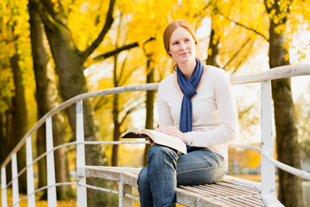 devotional: A smiling young woman holds a Bible in her hands and looks to her side in a city park by autumn.
