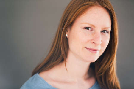 face shot: Young woman with red hair smiles at the camera.