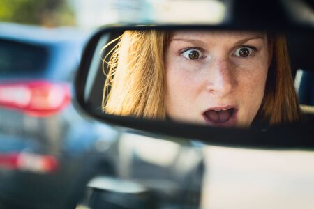 rear view mirror: Scared or shocked female driver in a car - reflection in the rear view mirror.