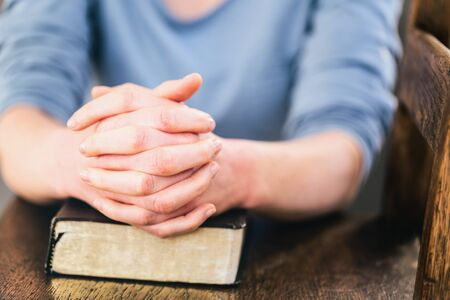 christian women: Praying hands of a woman over a closed Bible.