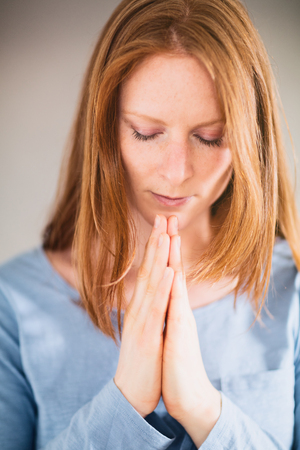 the believer: Portrait of a praying young woman.