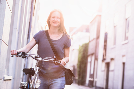 City lifestyle portrait of a smiling young woman pushing a bicycle on a narrow street. Natural sunlight.