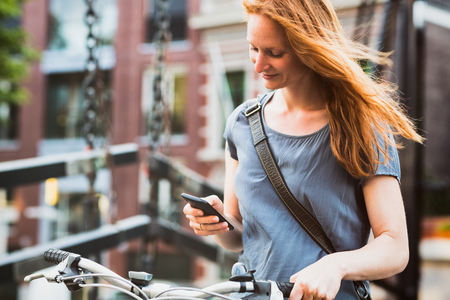 Casual young woman in a city holding a smartphone and a bicycle.