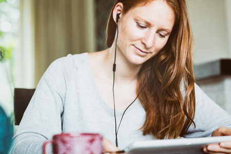 Woman using a tablet at home with attached headphones.