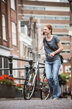 City life - a young woman talking on the phone and pushing a bicycle on a street in a European town. Stockfoto
