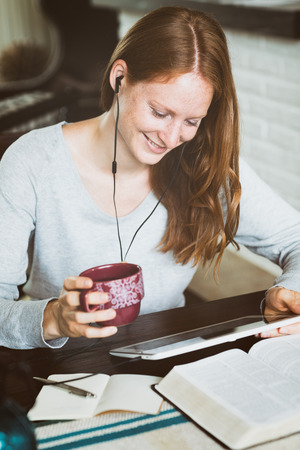 A smiling young woman studying the Bible at home with a tablet.
