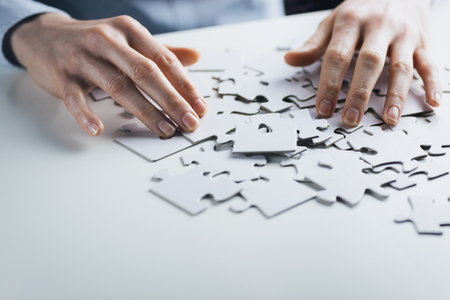 Businesswoman with a jigsaw puzzle on a white table. Stock Photo