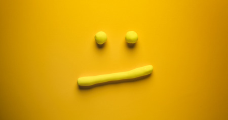 Thinking face - a yellow emoticon make out of modelling clay on a yellow background.