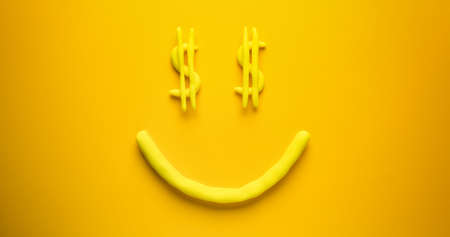 Seeing dollar signs face - a yellow emoticon make out of modelling clay on a yellow background. Reklamní fotografie