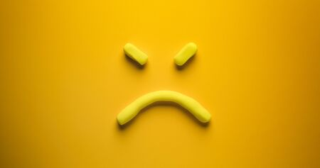 Angry face - a yellow emoticon make out of modelling clay on a yellow background.