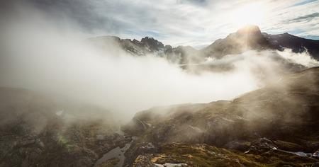 Lofoten Islands scenery by summer - the sunlight breaks through as clouds move in near Munken mountain top. Stock fotó