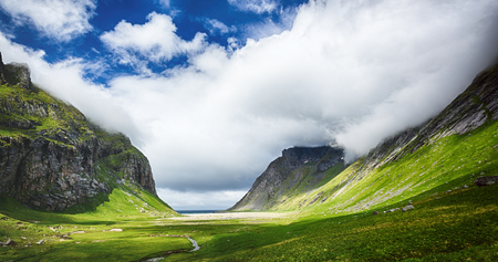 Lofoten Islands, Horseid beach by summer. Scenic landscape view of the valley leading to the beach.