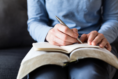 Bible study and Christianity - A woman takes notes as she reads from an open Bible at home.